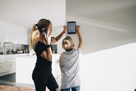 Teenage girl talking on phone using digital tablet by brother standing at home - MASF00911