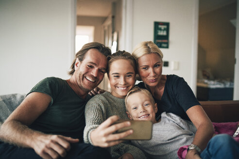Smiling family taking selfie through smart phone while sitting on sofa at home - MASF00926