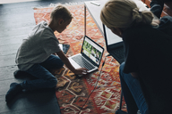 High angle view of woman looking at boy using laptop by coffee table in living room at home - MASF00944