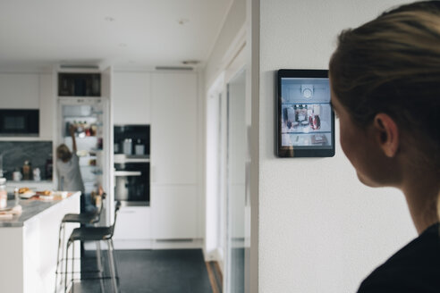 Rear view of teenage girl standing by wall with digital tablet looking at brother in kitchen - MASF00962