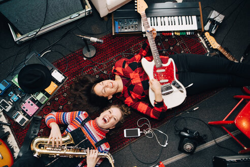 High angle view of happy female musicians playing instruments while lying on carpet - MASF00980
