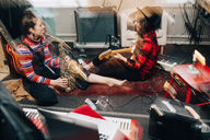 Smiling female musicians playing instruments while sitting on carpet at studio - MASF00983