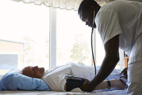 Side view of male nurse checking blood pressure of senior man on hospital bed against window - MASF01013