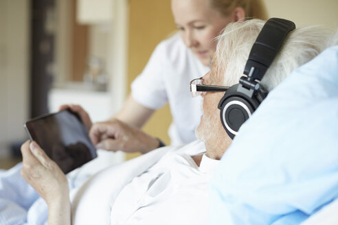 Senior man wearing headphones while using digital tablet with female nurse on hospital bed - MASF01019