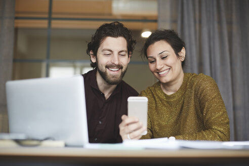 Smiling business colleagues using mobile phone at creative office - MASF01022