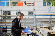 Side view of architect reading blueprint by incomplete building at construction site - MASF01028