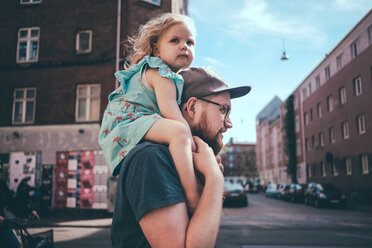 Side view of father carrying daughter on shoulders at city street - MASF01034