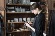 Side view of young female entrepreneur using digital tablet while standing by rack at store - MASF01055
