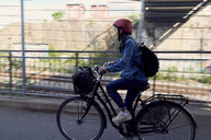 Side view of woman cycling on road in city - MASF01067