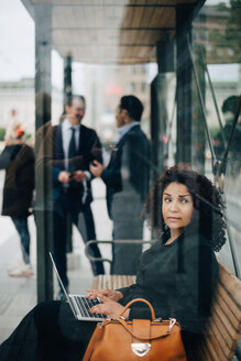 Side view of mid adult businesswoman looking away while sitting with laptop at bus shelter seen from glass - MASF01097