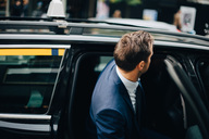 Side view of businessman entering taxi in city - MASF01103