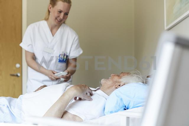 Smiling female nurse adjusting bed senior man's bed in hospital ward - MASF01127 - Maskot ./Westend61