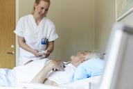 Smiling female nurse adjusting bed senior man's bed in hospital ward - MASF01127