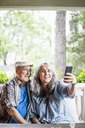 Smiling senior couple taking selfie in porch - MASF01157
