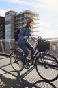 Smiling mid adult woman cycling on footbridge against sky - MASF01178