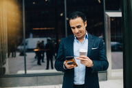 Smiling businessman using smart phone while holding disposable coffee cup against building in city - MASF01223