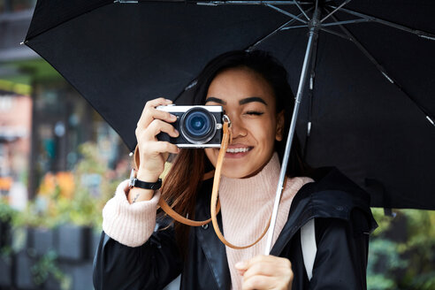 Smiling woman carrying umbrella photographing through camera in city - MASF01232