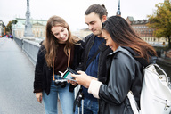 Smiling friends reading map while standing on bridge in city - MASF01235