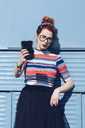 Redhead young woman taking selfie while standing against mini van - MASF01264
