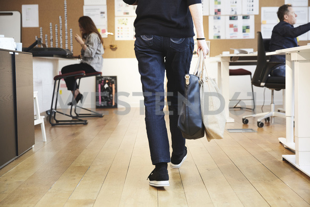Rear view of senior female professional walking with purse and bag amidst colleagues in creative office - MASF01282