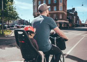 Rear view of father cycling while daughter sitting on back seat at city street - MASF01294
