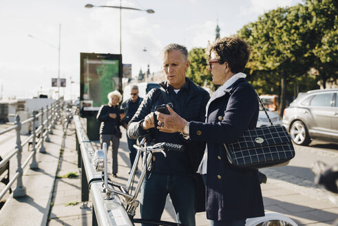 Senior couple using mobile phone while standing on sidewalk in city - MASF01333