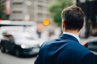 Rear view of mature businessman looking away while standing in city - MASF01342