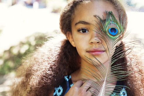 Close-up portrait of girl holding peacock feather - CAVF35221