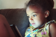 Close-up of girl using tablet computer while sitting on sofa at home - CAVF35239