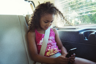 Girl using smart phone while traveling in car - CAVF35245