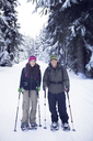 Portrait of couple wearing snowshoes - CAVF35281