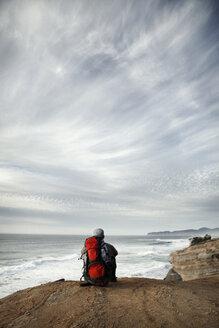 Man sitting on edge of cliff - CAVF35353
