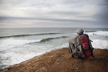 Man sitting on edge of cliff - CAVF35356