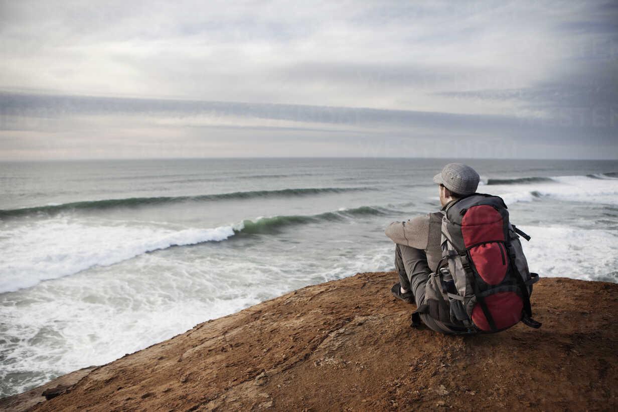 Man sitting on edge of cliff - CAVF35356 - Cavan Images/Westend61