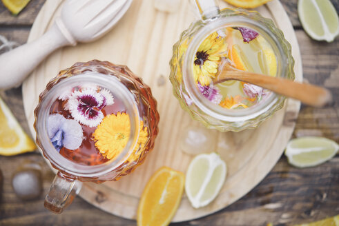 Refreshing mineral water with edible flowers, Viola wittrockiana, Dianthus caryophyllus, Calendula officinalis, lemon and orange - SKCF00411