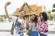 Thailand, Bangkok, three friends with street food taking selfie - WPEF00184