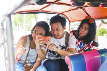 Thailand, Bangkok, three friends riding tuk tuk taking pictures with smartphone - WPEF00187