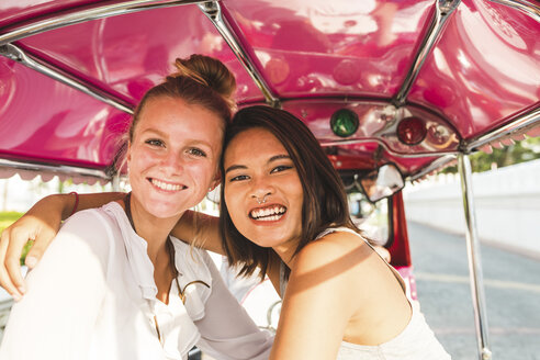 Thailand, Bangkok, portrait of two happy two friends riding tuk tuk - WPEF00196