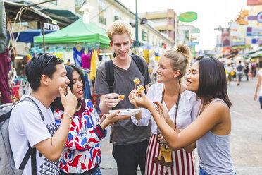 Thailand, Bangkok, Khao San Road, group of friends tasting local food on street market - WPEF00205