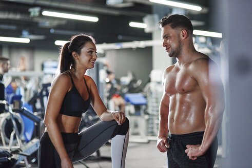 Smiling man and woman talking at the gym - ABIF00237