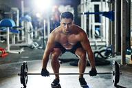 Man lifting barbell in gym - ABIF00240