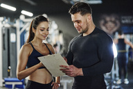 Personal trainer talking to woman in gym - ABIF00246