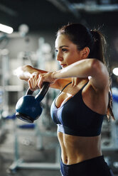 Woman exercising with a kettlebell in gym - ABIF00252