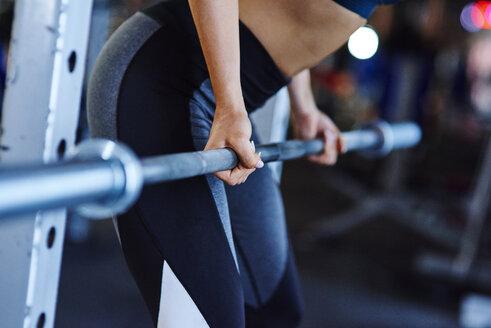 Woman lifting barbell in gym - ABIF00255