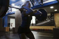 Woman lifting barbell in gym - ZEDF01259