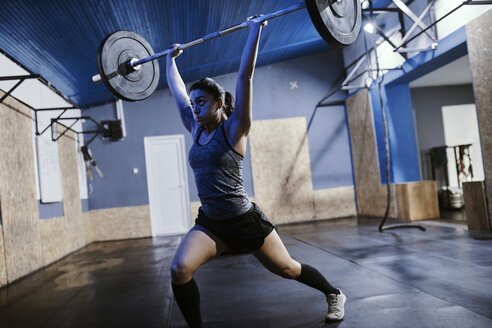 Woman lifting barbell in gym - ZEDF01262