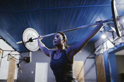 Woman lifting barbell in gym - ZEDF01265