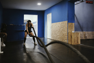 Woman exercising with ropes in gym - ZEDF01268