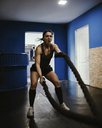 Woman exercising with ropes in gym - ZEDF01271