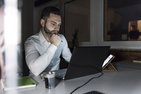 Businessman working on laptop in office at night - UUF13195